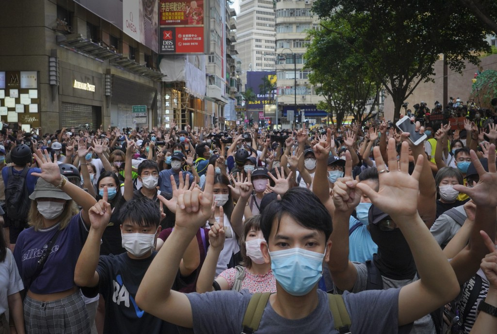 """FILE - In this Wednesday, July. 1, 2020 file photo, protesters against the new national security law gesture with five fingers, signifying the """"Five d..."""
