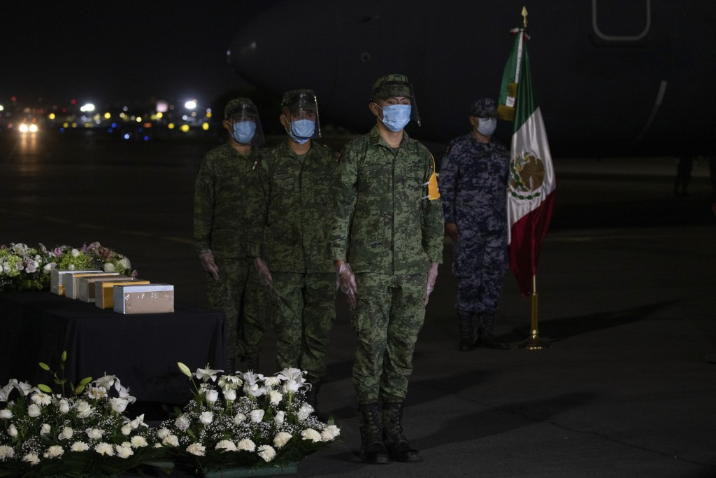 Mexican soldiers mourn five boxed cremated remains, of Mexicans who died from COVID-19, during a welcoming ceremony at the tarmac of Benito Suarez Int...