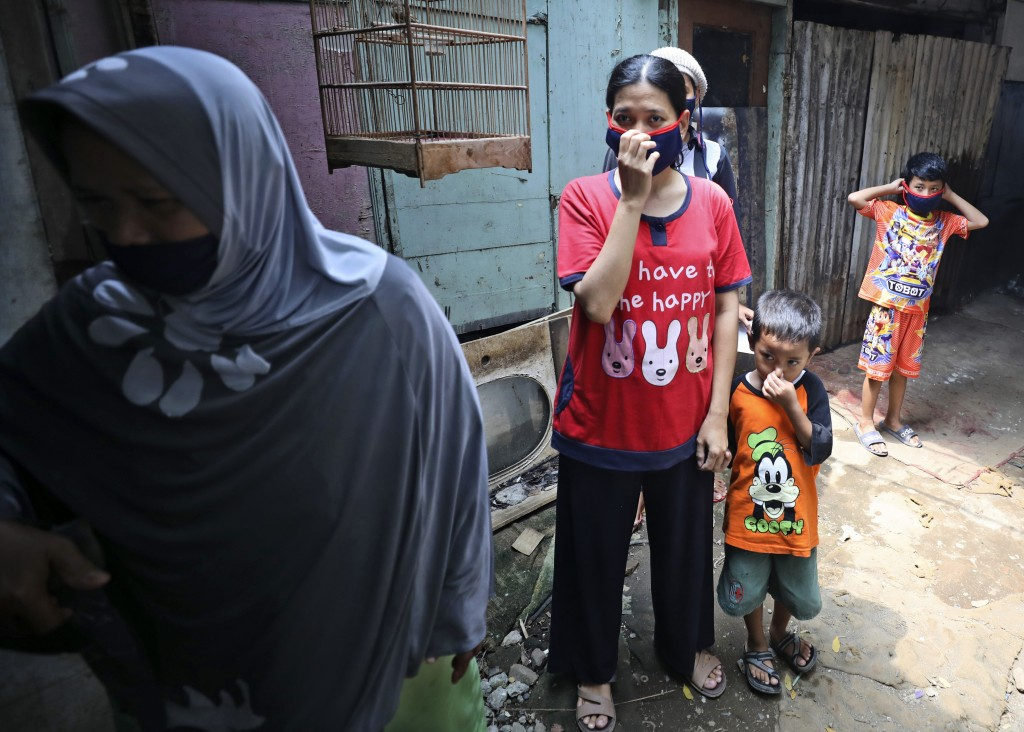 People cover their nose and mouth as workers fumigate their neighborhood to prevent a dengue fever outbreak in a slum in Jakarta, Indonesia, Wednesday...
