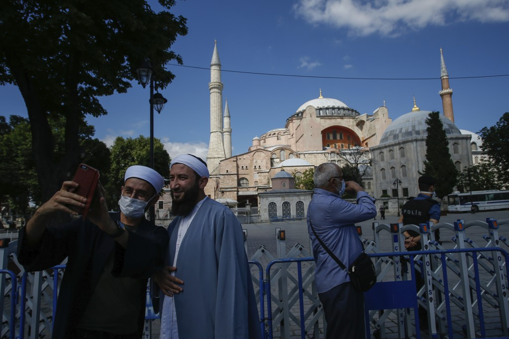 People use their mobile to take a selfie picture outside the now closed Byzantine-era Hagia Sophia, one of Istanbul's main tourist attractions in the ...