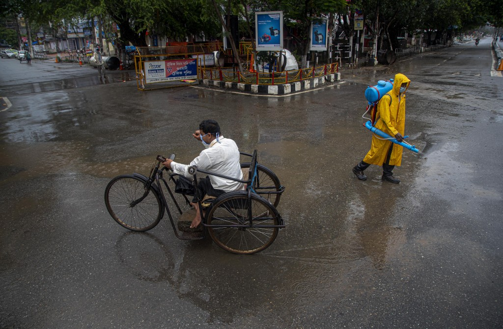A man rides on a tricycle past a civic worker sanitizing a deserted road during a fresh lockdown imposed in Gauhati, Assam state, India, Sunday, July ...