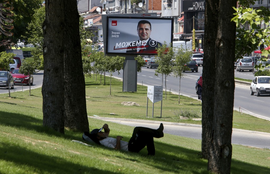 A man rests under a tree near an electoral poster of the leader of the ruling Social Democrats Zoran Zaev, in a street in Skopje, North Macedonia on S...