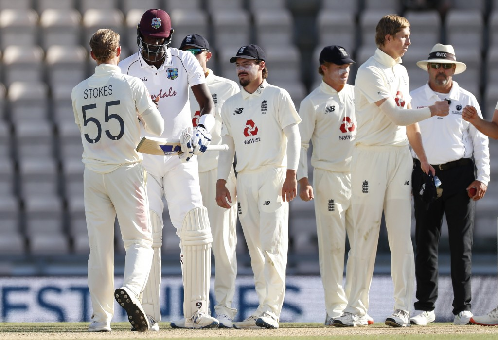 West Indies captain Jason Holder, second left, greets England captain Ben Stokes, left, after winning the first cricket Test match between England and...