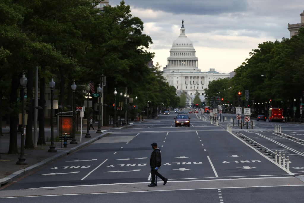 FILE - In this May 6, 2020, file photo a man walks across Pennsylvania Avenue Northwest in Washington. Despite pandemic conditions that made normal si...