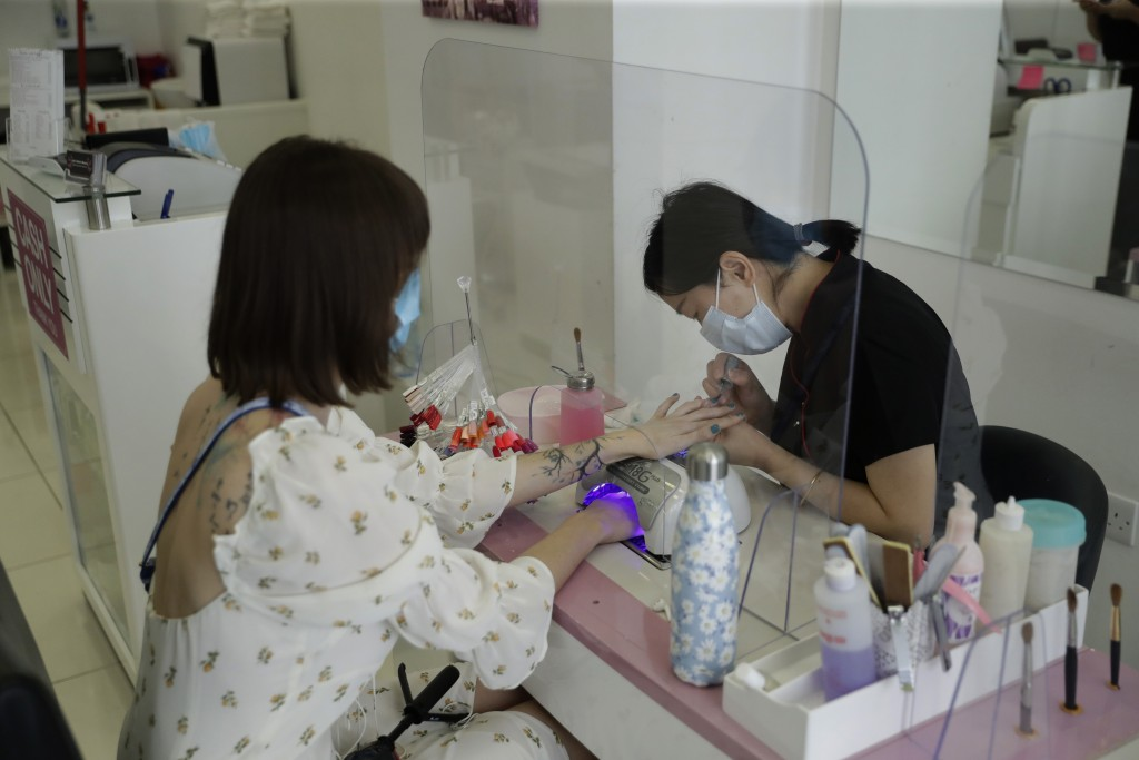 A customer receives a Gelish manicure at Lily's Nails & Beauty on Clerkenwell Road in London, Monday, July 13, 2020. Nail bars, beauty salons, tattoo ...