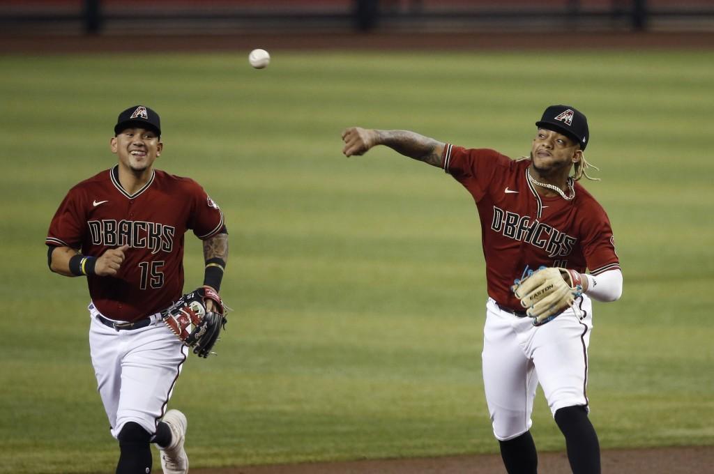 Arizona Diamondbacks shortstop Ketel Marte, right, throws the baseball to a teammate as second baseman Ildemaro Vargas (15) looks on during a training...