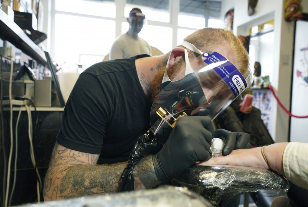 Tattoo artist Anth Matthews starts work on a tattoo at the Axe & Anchor tattoo shop as they reopen in North Shields, England, Monday July 13, 2020. Na...
