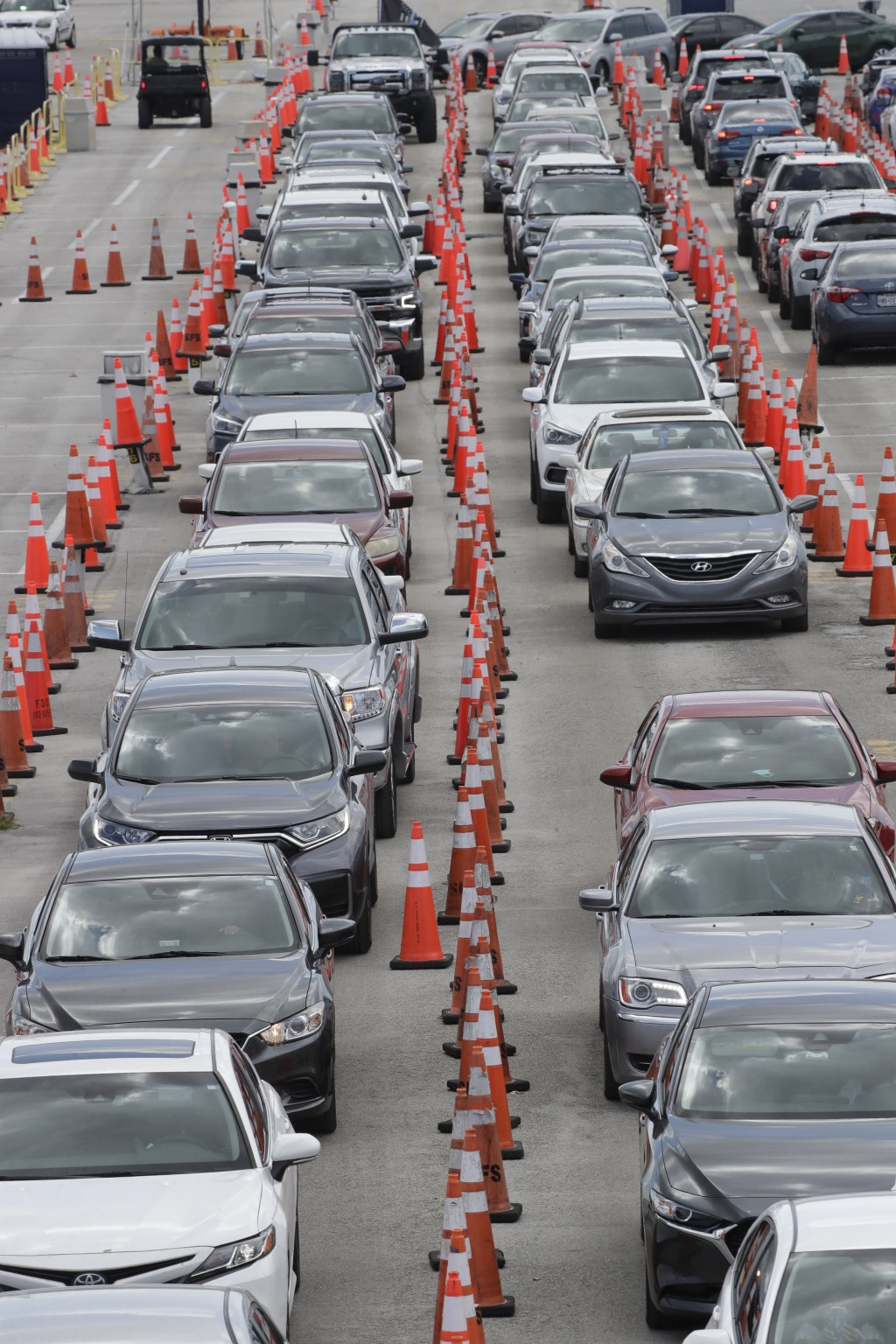 FILE - Cars wait in line at a drive-through COVID-19 testing site outside Hard Rock Stadium, in a Wednesday, July 8, 2020 file photo, in Miami Gardens...