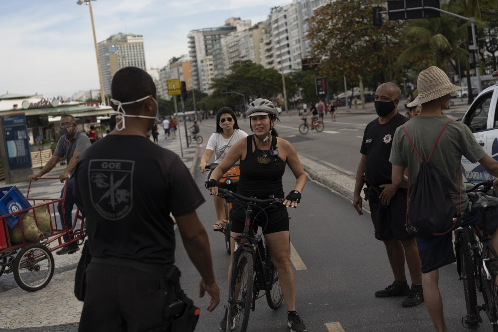 A municipal guard stops a woman on a bike to tell her to wear a mask at Copacabana beach amid the outbreak of the new coronavirus in Rio de Janeiro, B...