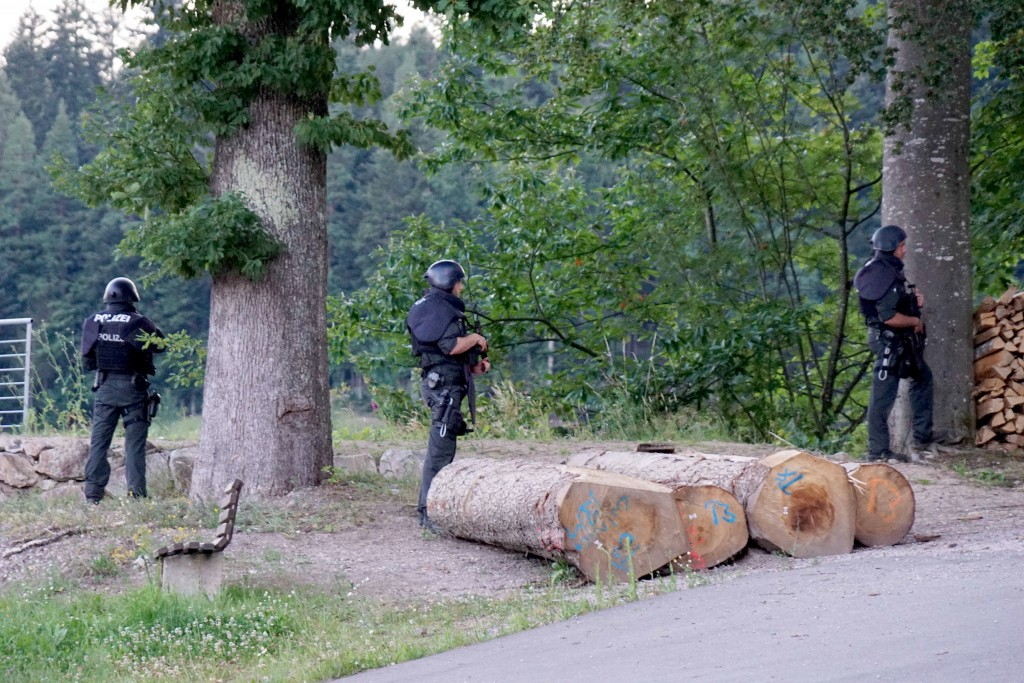 Police officers stay outside a wooded area on a road near Oppenau, Germany, Monday, July 13, 2020. Authorities in Germany say they have deployed hundr...