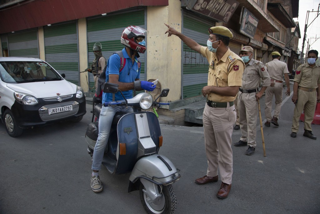 An Indian police officer asks a civilian to take an alternative road as they block traffic in Srinagar, Indian controlled Kashmir, Monday, July 13, 20...