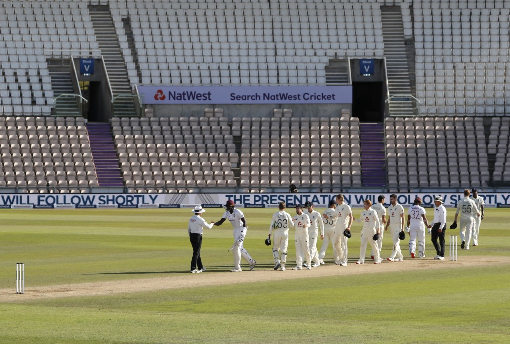 West Indies captain Jason Holder, second left, greets the umpire after winning the first cricket Test match between England and West Indies, at the Ag...
