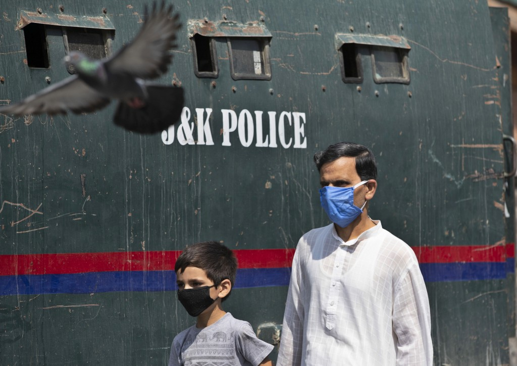 A Kashmiri man and a child wearing masks walk past a parked armored police vehicle in Srinagar, Indian controlled Kashmir, Monday, July 13, 2020. Auth...
