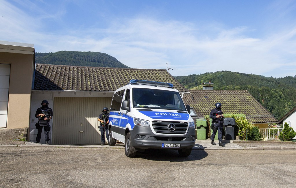 Police officers stay next to a police car in Oppenau, Germany, Monday, July 13, 2020. Authorities in Germany say they have deployed hundreds of police...