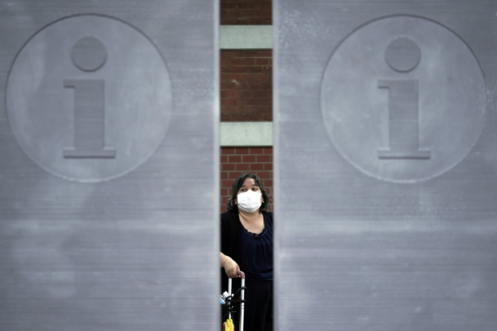 A woman wearing a face mask to help curb the spread of the coronavirus walks Monday, July 13, 2020, in Tokyo. The Japanese capital has confirmed more ...