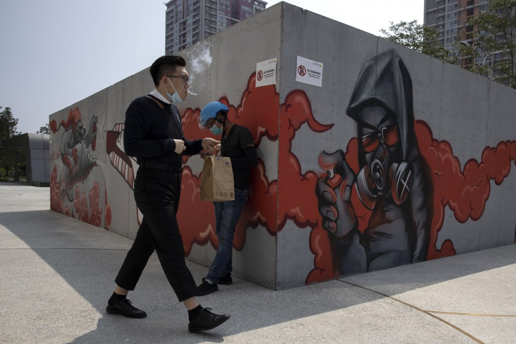 A man lowers his mask to smoke as he walks past graffiti artwork in Beijing Monday, July 13, 2020. China reported eight new cases, all of them brought...