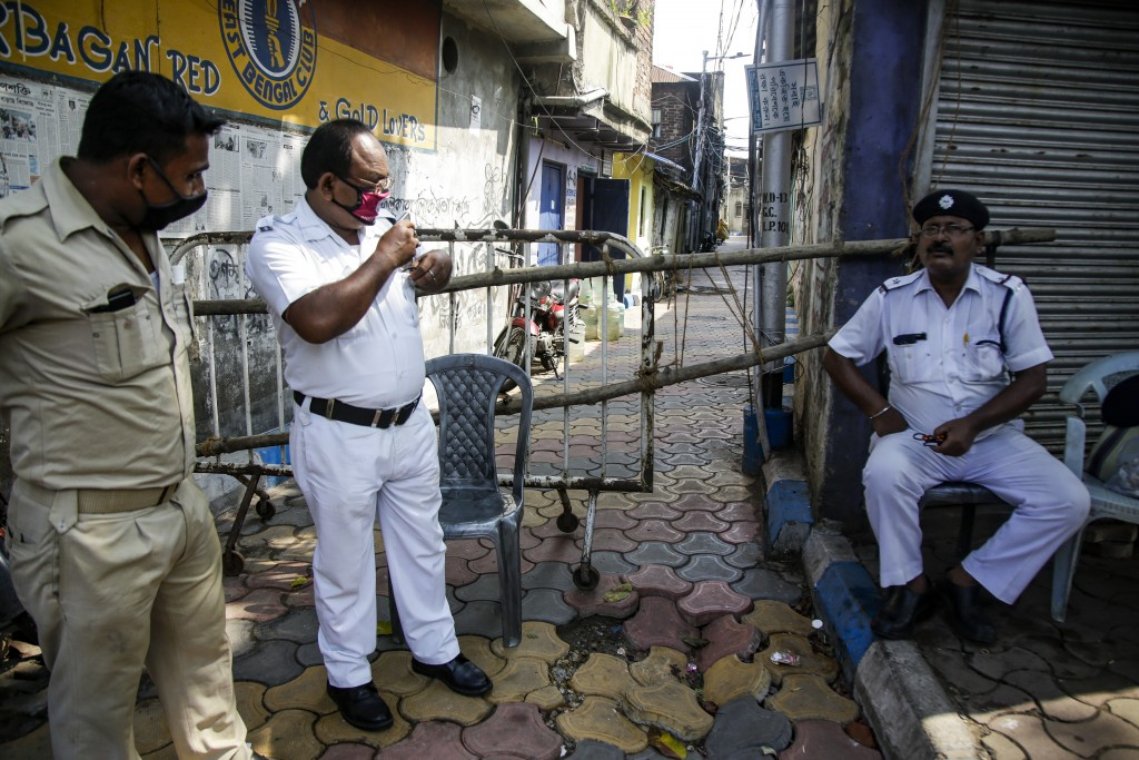 Policemen keep vigil outside a barricaded alley of a containment zone in Kolkata, India, Tuesday, July 14, 2020. Several Indian states imposed weekend...