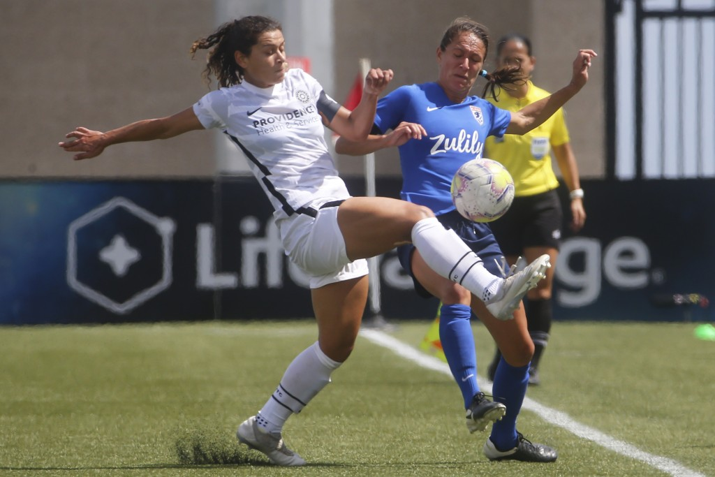Portland Thorns midfielder Rocky Rodriguez, left, and OL Reign defender Steph Cox, right, fight for the ball during the first half of an NWSL Challeng...