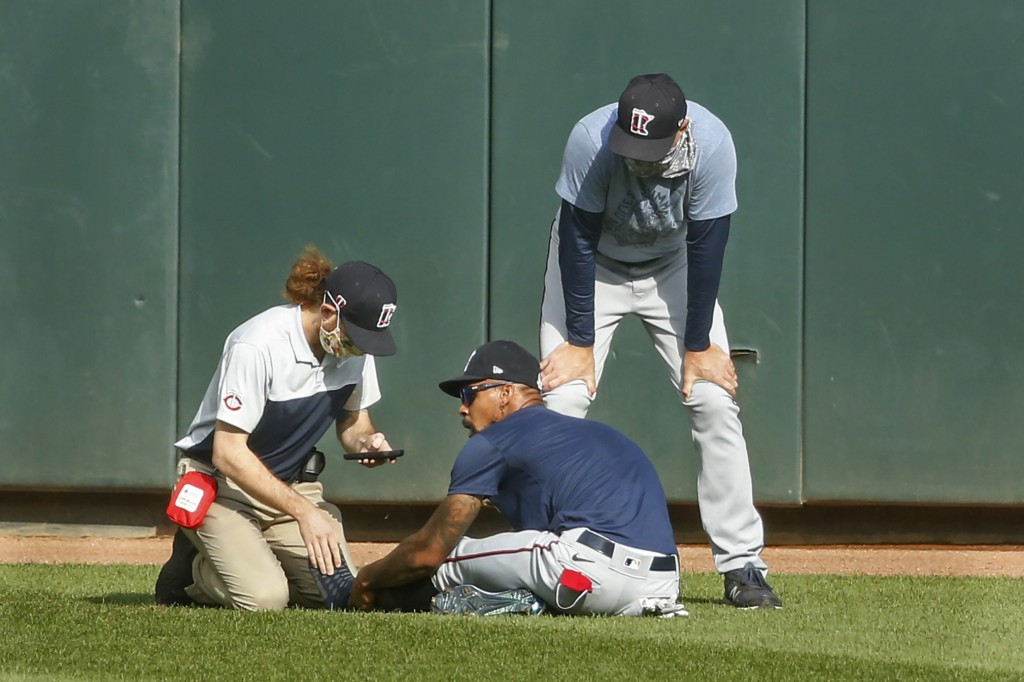 Minnesota Twins' Byron Buxton, center, holds his ankle after he stumbled during an intrasquad game at baseball practice Monday, July 13, 2020, in Minn...