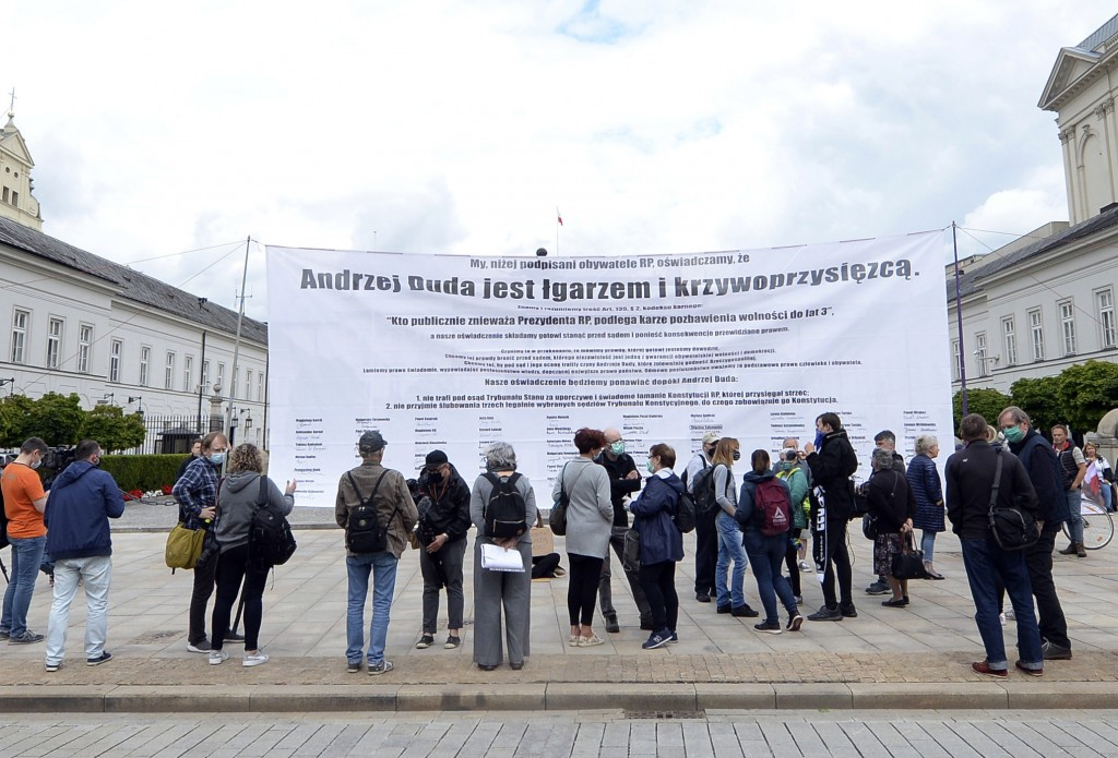 "A small group of protesters with a banner reading ""Andrzej Duda is a mocker and perjurer"" hold a small rally against the narrow re-election of Preside..."