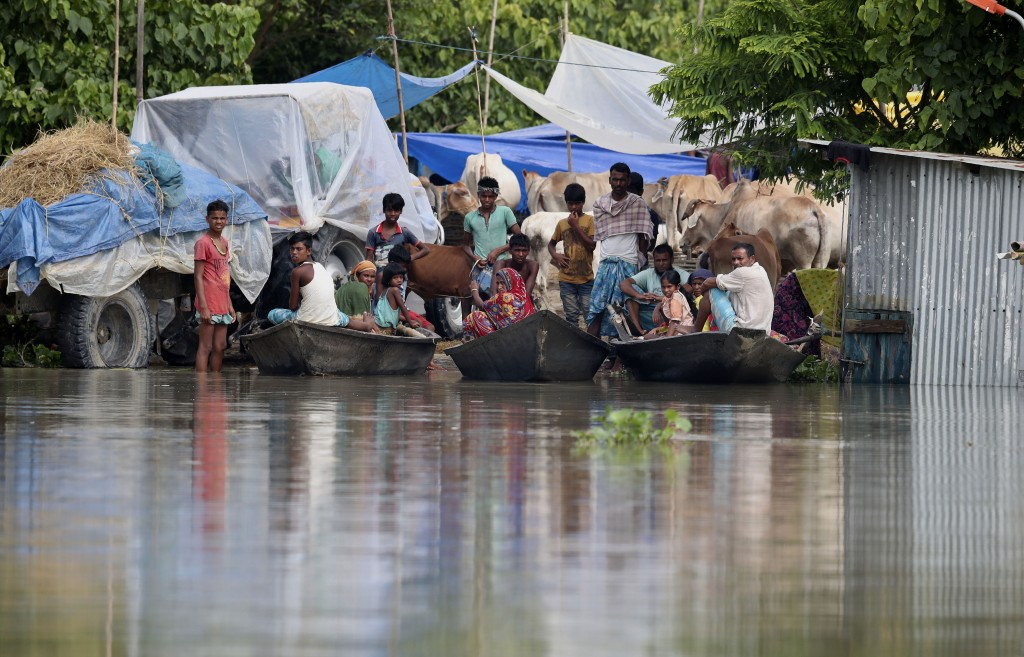 Indian flood affected villagers and cattle take shelter on a partially washed away road in Gagolmari village, Morigaon district, Assam, India, Tuesday...