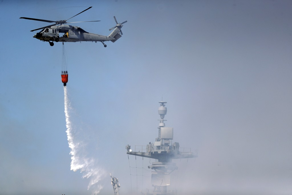 A helicopter drops water on the USS Bonhomme Richard Monday, July 13, 2020, in San Diego. Fire crews continue to battle the blaze Monday after 21 peop...