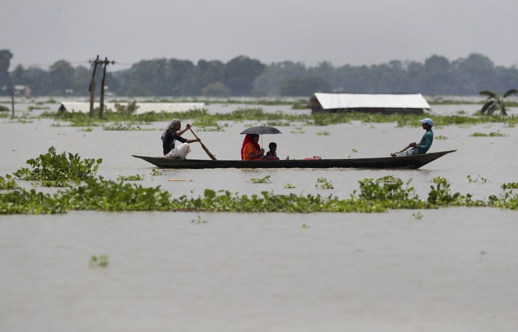 A family travels in a country boat over floodwaters in Gagolmari village, in Morigaon district of Assam, India, Tuesday, July 14, 2020. Hundreds of th...
