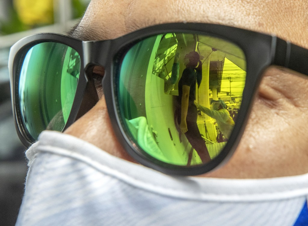 Health workers collecting a nasal swab from a woman are reflected on the sunglasses in Rayong province, Thailand, Tuesday, July 14, 2020. Authorities ...