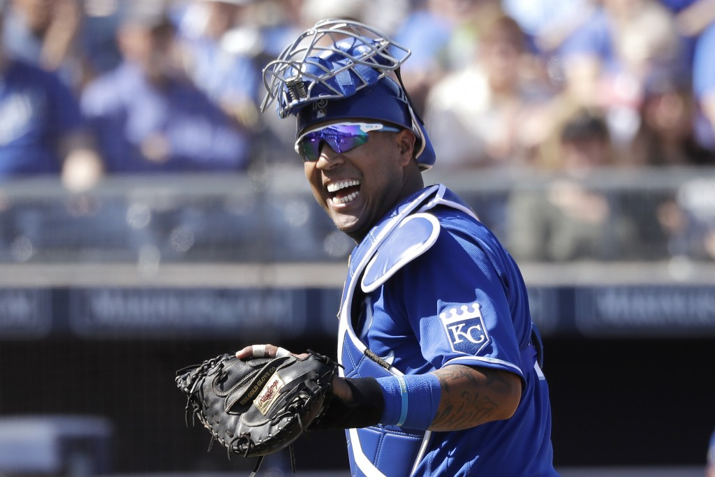 FILE - In this Wednesday, March 4, 2020, file photo, Kansas City Royals catcher Salvador Perez smiles as he turns to a teammate who made an out on a d...