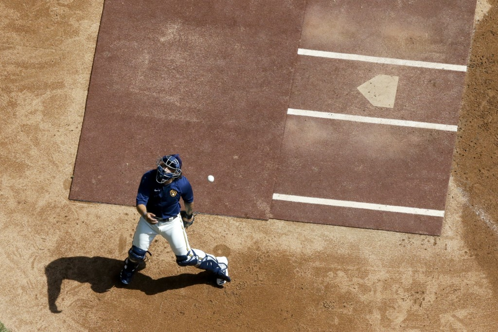 Milwaukee Brewers' Jacob Nottingham tries to catch a ball during a practice session Monday, July 13, 2020, at Miller Park in Milwaukee. (AP Photo/Morr...