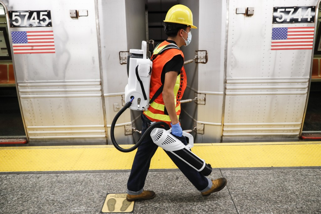 A contractor carries an electrostatic sprayer used to disinfect subway cars at the 96th Street station to control the spread of COVID-19, Thursday, Ju...