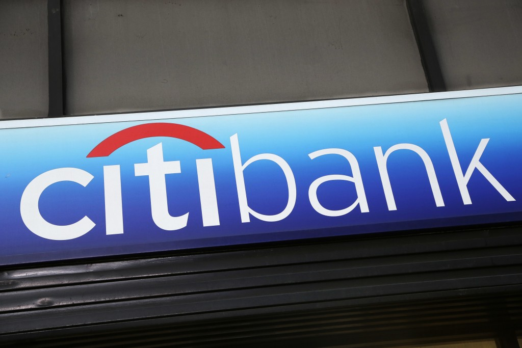 FILE - In this Jan. 15, 2015, file photo, a Citibank sign hangs above a branch office in New York.  The tens of millions of consumers and businesses o...