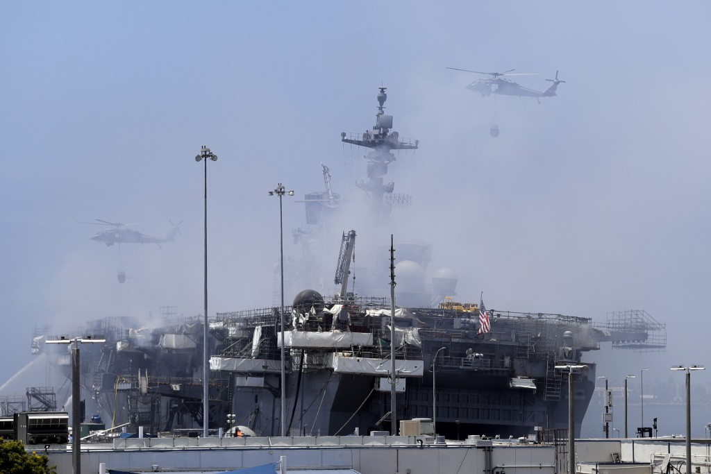 Helicopters approach the USS Bonhomme Richard as crews fight the fire Monday, July 13, 2020, in San Diego. Fire crews continue to battle the blaze Mon...