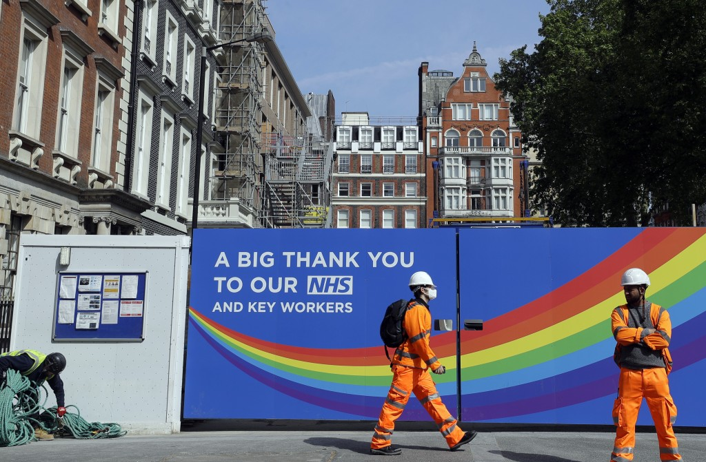 FILE - In this Thursday, May 7, 2020 file photo, a  construction worker passes a sign thanking the NHS in London, as the country in is lockdown to pre...