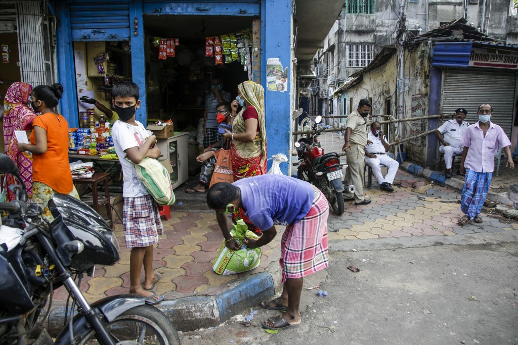 People buy essentials from a grocery shop just outside a containment zone barricaded, right, to prevent the spread of the coronavirus in Kolkata, Indi...