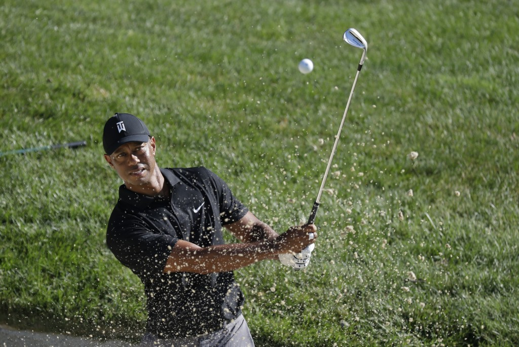 Tiger Woods hits out of a bunker on the 15th hole during a practice round for the Memorial golf tournament, Tuesday, July 14, 2020, in Dublin, Ohio. (...