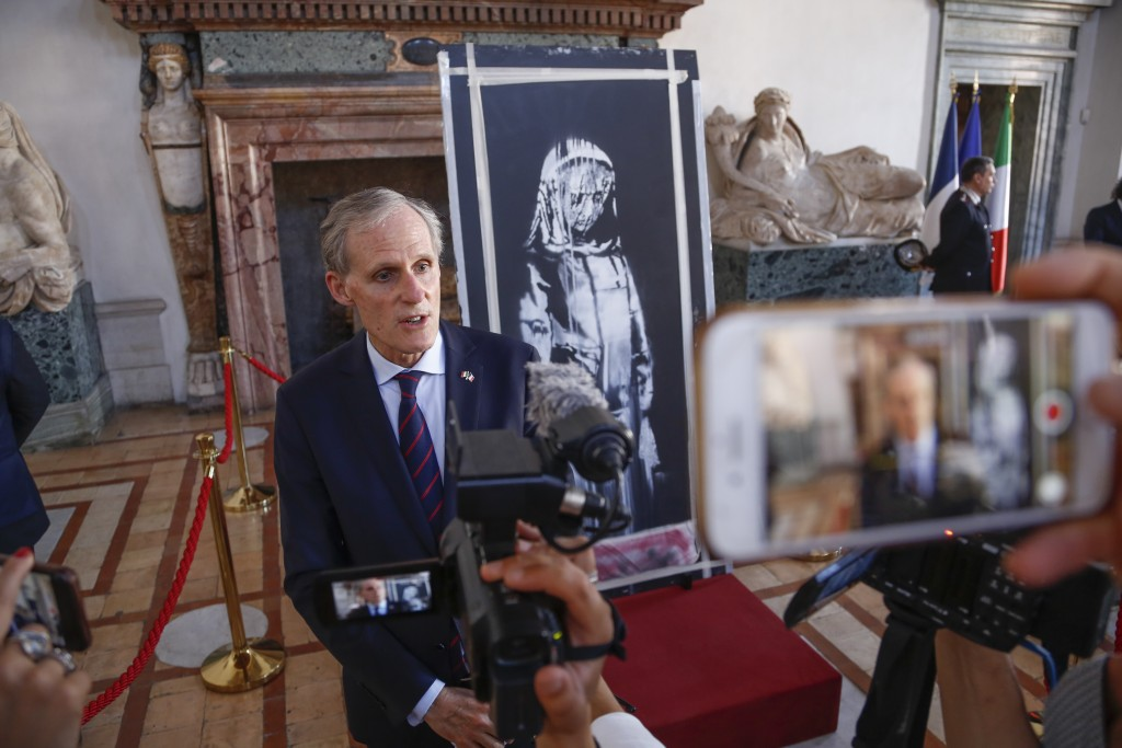 Franch Ambassador to Italy, Christian Masset, stands by a recovered stolen artwork by British artist Banksy, depicting a young female figure with a mo...