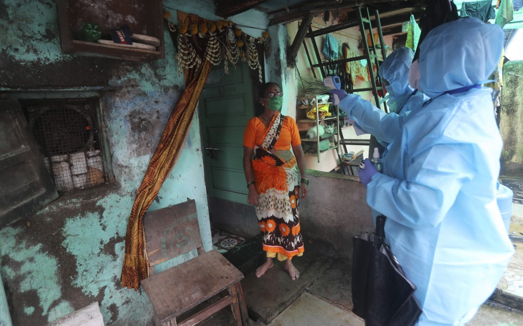 Health workers screen people for COVID-19 symptoms at a slum in Mumbai, India, Tuesday, July 14, 2020. Several Indian states imposed weekend curfews a...