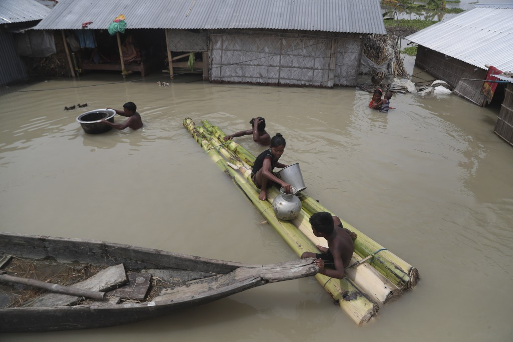 Flood affected villagers are seen near their partially submerged houses in Gagolmari village, Morigaon district, Assam, India, Tuesday, July 14, 2020....