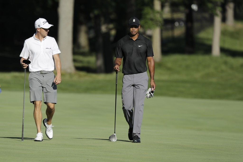 Justin Thomas, left, and Tiger Woods walk down the 13th fairway during a practice round for the Memorial golf tournament, Tuesday, July 14, 2020, in D...