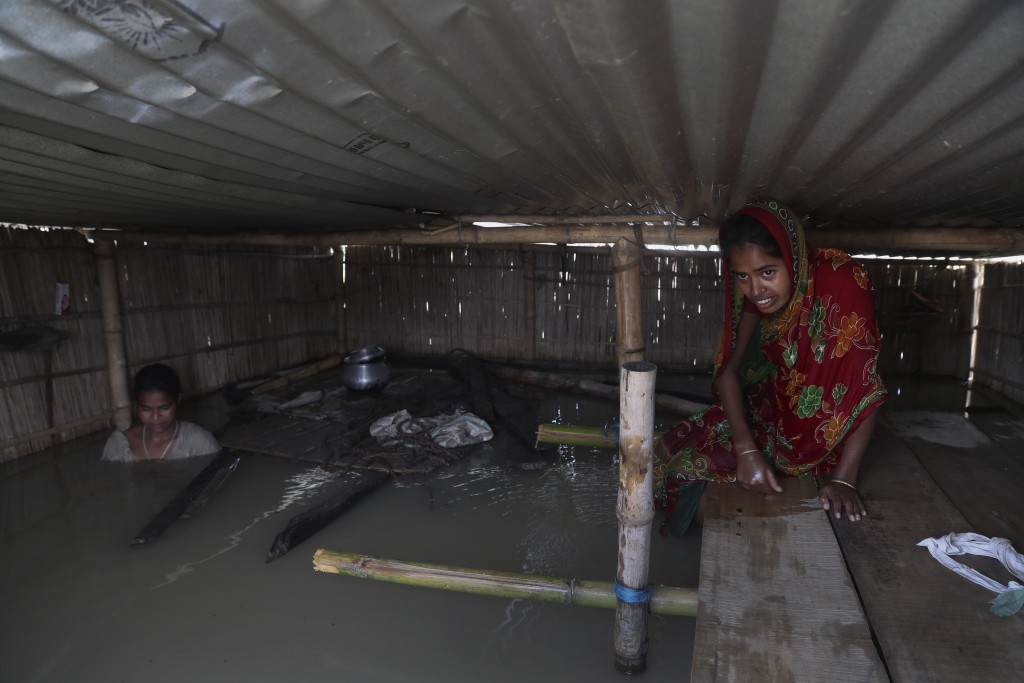 Indian flood affected villagers are seen inside their partially submerged houses in Gagolmari village, Morigaon district, Assam, India, Tuesday, July ...
