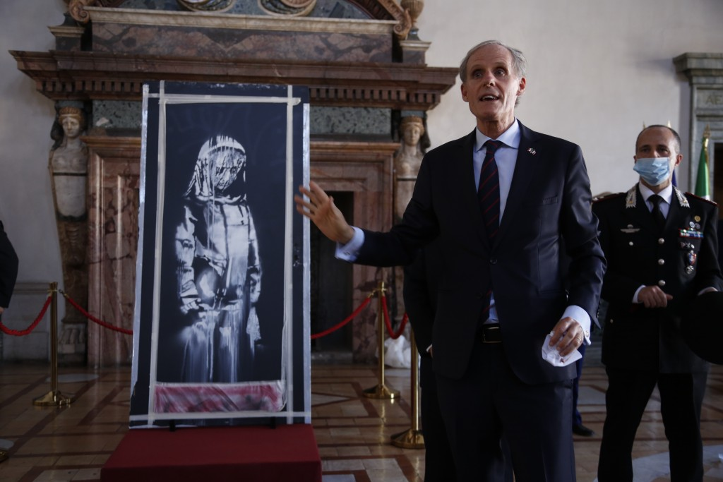Franch Ambassador to Italy, Christian Masset, unveils a recovered stolen artwork by British artist Banksy, depicting a young female figure with a mour...