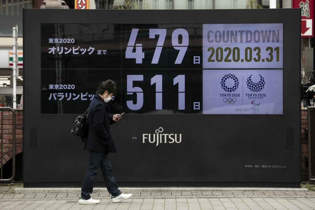 FILE - In this March 31, 2020, file photo, a man walks past a countdown display for the Tokyo 2020 Olympics and Paralympics in Tokyo. The countdown cl...