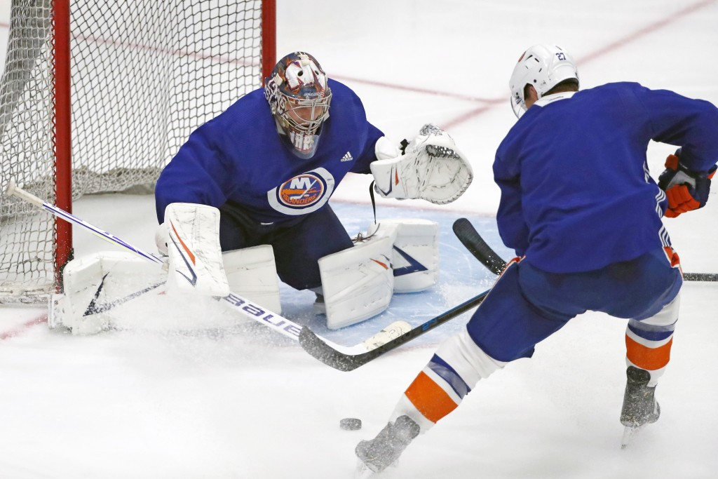New York Islanders goaltender Semyon Varlamov, left, prepares for a shot by Islanders left wing and captain Anders Lee during an NHL hockey team pract...