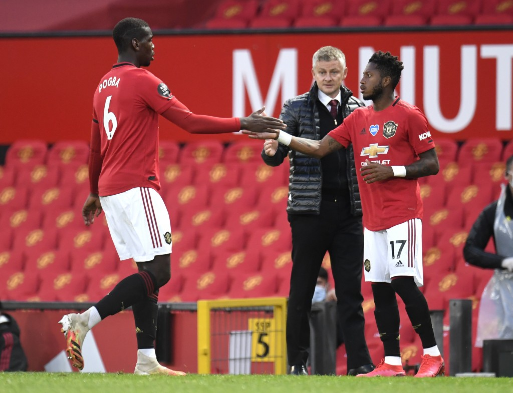 Manchester United's Paul Pogba, left, gestures to teammate Fred as he is substituted during the English Premier League soccer match between Manchester...