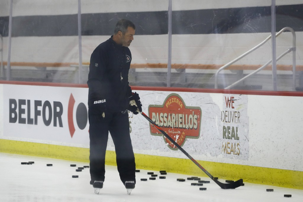 Philadelphia Flyers head coach Alain Vigneault gathers pucks during training camp at the NHL hockey team's practice facility Monday, July 13, 2020, in...