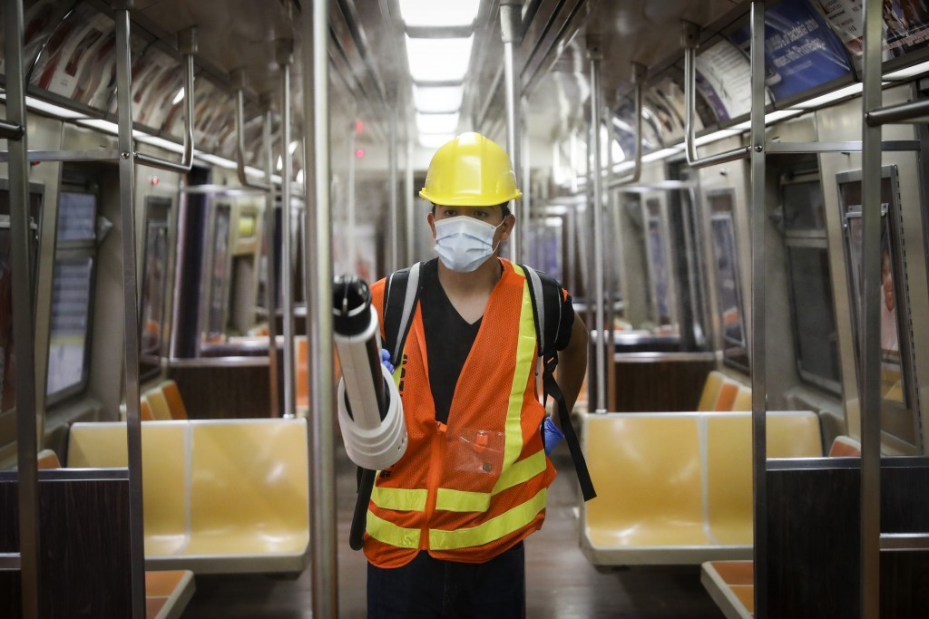 A contractor uses an electrostatic sprayer to disinfect subway cars at the 96th Street station to control the spread of COVID-19, Thursday, July 2, 20...