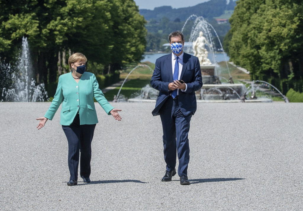 German Chancellor Angela, left, and Markus Soeder, right, Governour of the German state of Bavaria, arrive at the Herrechiemsee island, Germany, Tuesd...