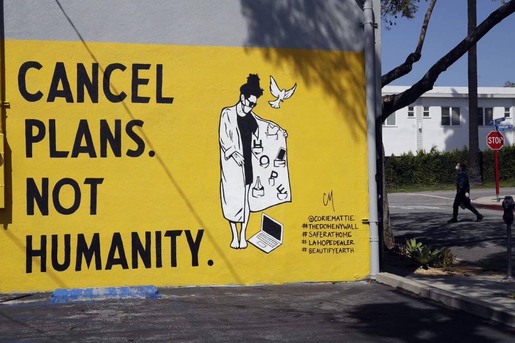 """A sign reads """"Cancel Plans Not Humanity"""" Tuesday, April 14, 2020, in Los Angeles. Murals with themes centered around the coronavirus have been popping..."""