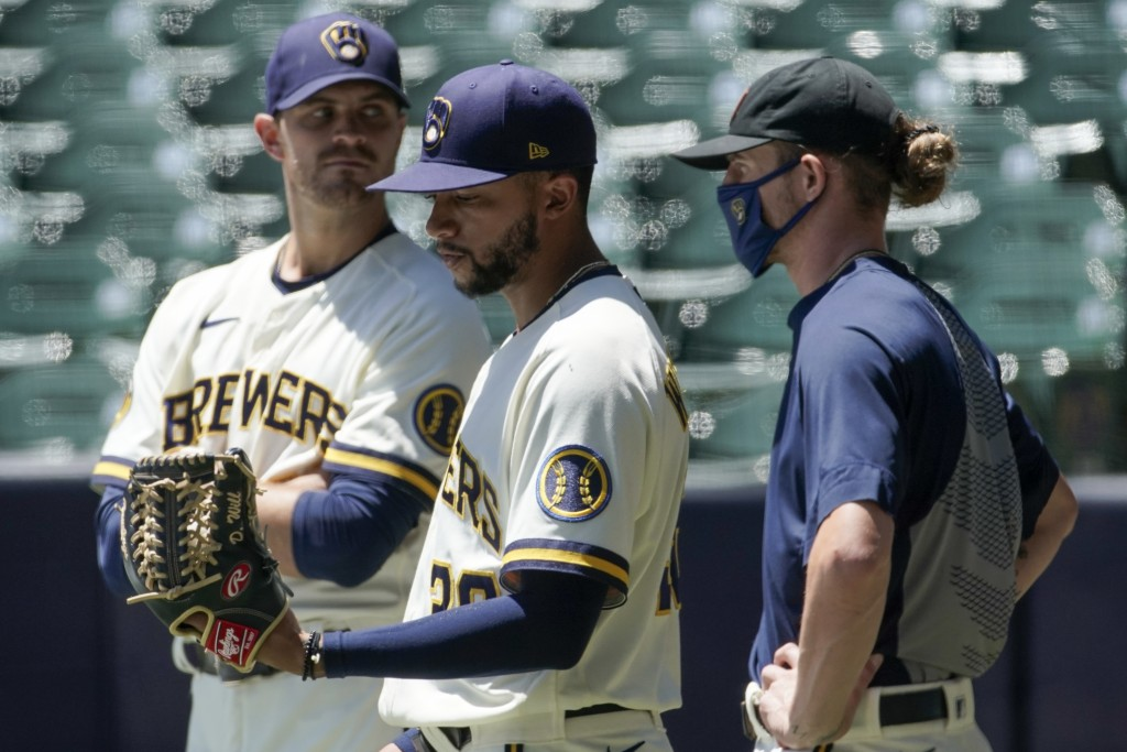 Milwaukee Brewers' Justin Grimm, Devin Williams and Josh Hader watch during a practice session Monday, July 13, 2020, at Miller Park in Milwaukee. (AP...